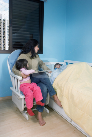 Mother and Kids stock photo, Mother reading a story to her children at bedtime by Orange Line Media