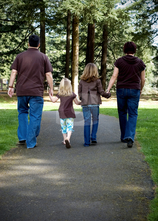 Family of Four stock photo, Family of four walking hand in hand away from the camera. Vertically framed shot. by Orange Line Media