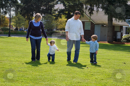 Family of Four in Park - Horizontal stock photo, Horizontally framed shot of an attractive family of four, two parents and two young boys, walking through a grassy park. by Orange Line Media