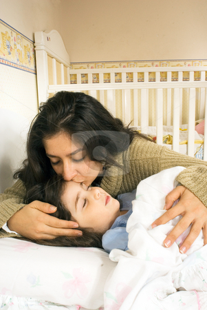 A Mother Kissing Her Daughter stock photo, A mother kissing her daughter goodnight. by Orange Line Media