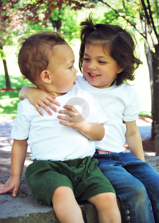 Brother and Sister stock photo, Brother and sister sitting with their arms around each other on a sunny day in the park. by Orange Line Media