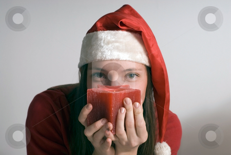 Woman with Christmas Candle - Horizontal stock photo, Horizontally framed shot of an attractive woman in a santa hat looking seductively at the camera over a red candle by Orange Line Media