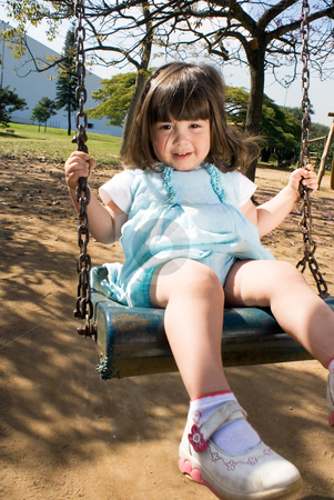 Little Girl Swinging stock photo, Cute little girl playing on a swing on a sunny day. Vertically framed shot. by Orange Line Media