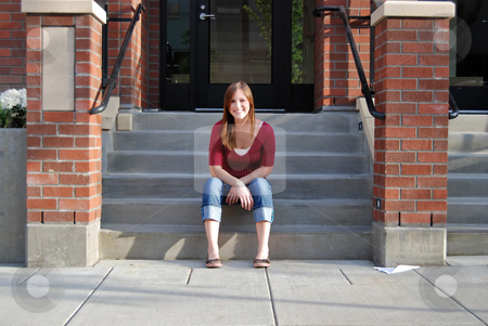 Smiling Teen Sitting on Stairs - Horizontal stock photo, Horizontally framed outdoor shot of a smiling teenage girl sitting on a buildings entryway stairs. by Orange Line Media