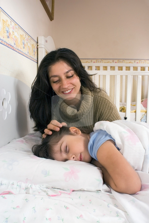 Mother and Daughter - Vertical stock photo, Vertically framed shot of a mother putting her daughter to bed. by Orange Line Media