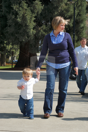 Walking with Mom stock photo, Toddler boy and his mother holding hands walking outdoors. by Orange Line Media