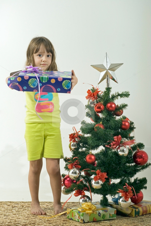 Girl and Christmas Tree stock photo, Girl holding out present standing next to a christmas tree. by Orange Line Media