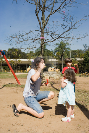Mother and Children stock photo, Mother blowing bubbles with her youngest daughter while her son does the same in the background by Orange Line Media