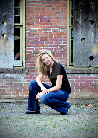 Cute Blond stock photo, Attractive blond woman crouching down in front of an old brick building. Vertically framed shot by Orange Line Media