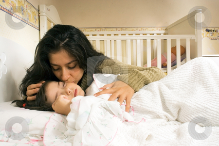 Mother and Daughter stock photo, Attractive mother kissing her sleeping daughter's forehead. Horizontally framed shot by Orange Line Media