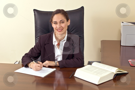 Female Executive stock photo, Businesswoman wearing a blazer sitting at her desk in her office and smiling at the camera. Horizontally framed shot. by Orange Line Media