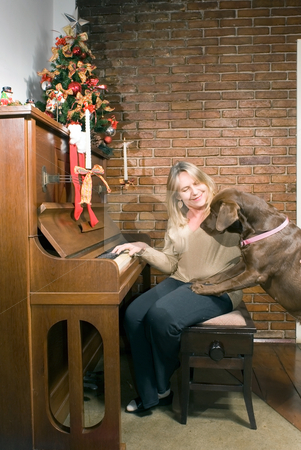 Family Christmas stock photo, Older woman sitting at an upright piano at Christmas time getting ready to play while the family dog looks on curiously by Orange Line Media