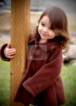Cute Girl Smiling stock photo, Cute young girl in a brown coat smiling as she holds on to a fence post outdoors by Orange Line Media