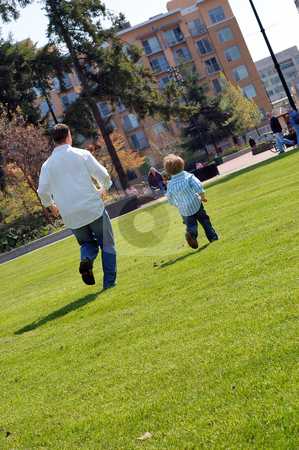 Father Chasing His Son stock photo, Vertically framed shot of a father chasing his son in park with lots of green grass. by Orange Line Media