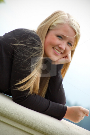 Smiling Teen Girl on Balcony stock photo, Outdoor, close-up shot of a smiling teenage girl, with blond hair and blue eyes, leaning against a balcony's edge. by Orange Line Media