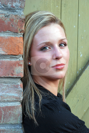Attractive Woman Looking to the Side - Vertical stock photo, Vertically framed shot of an attractive woman, leaning against a brick wall, with her head turned 90 degrees looking at the camera. by Orange Line Media