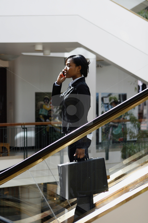 Businesswoman on Phone on Escalator - Vertical stock photo, Side shot of a businesswoman, talking on cellphone, riding an escalator down a floor. by Orange Line Media