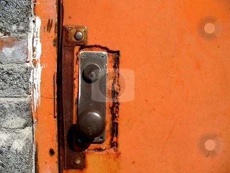 Rusted Doorknob on Steel Door stock photo, Close-up shot of a rusting doorknob and lock on a orange steel door set in cinderblock building. by Orange Line Media