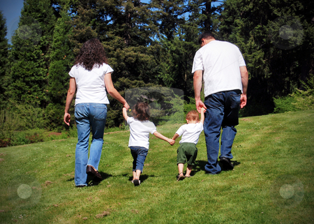 Family Fun stock photo, Family of four walking hand in hand away from the camera. by Orange Line Media