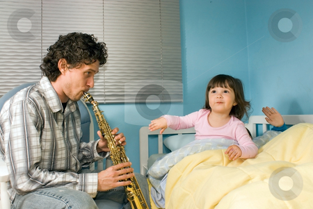A Father Playing Soprano Saxophone for His Children - Horizontal stock photo, Horizontally framed shot of a father playing a soprano saxophone for his children in a bedroom. by Orange Line Media