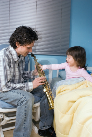 Father and Daughter stock photo, Little girl reaching out to grab her father's saxophone while he plays her a lullaby by Orange Line Media