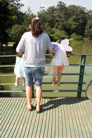 Mother and Daughters stock photo, Mother and her two daughters looking over the railing of a bridge on a sunny day. Vertically framed shot. by Orange Line Media