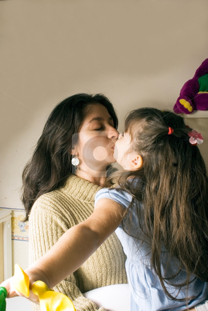 A Mother and a Daughter Kissing stock photo, A mother kissing her daughter. by Orange Line Media