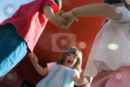 Family Fun stock photo, Siblings dancing in a circle while being photographed from a low-angle. by Orange Line Media