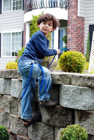 Budding Rock Climber stock photo, Adorable little boy top roping and climbing a stone garden wall using bungee cords as climbing rope. Vertically framed shot. by Orange Line Media