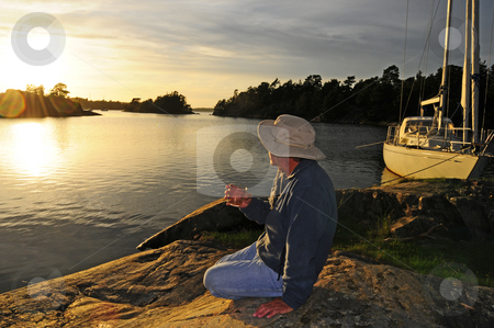 Enjoy life stock photo, Sailor enjoys a whiskey watching the sunset by Magnus Johansson