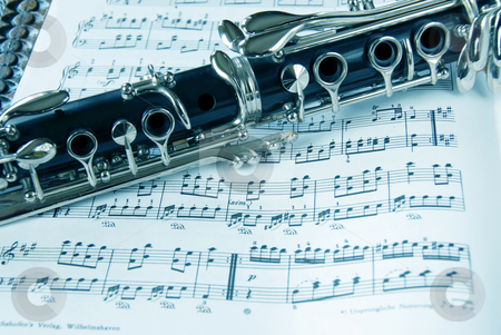 Classic music stock photo, Fragment of black shining clarinet over opened music book by Julija Sapic