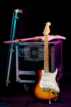 Two electric guitars with a crate and a case on a stage with lig stock photo, Two electric guitars with a crate and a case on a stage with lights by Vince Clements