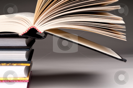 A horizontal view of a stack of books with one open on a gray ba stock photo, A horizontal view of a stack of books with one open on a gray background by Vince Clements