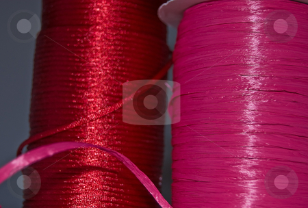 Two Large Spools of Ribbon stock photo, Two large spools of ribbon, one bright pink raffia, the other a deep red rat tail.  This photo also shows curves and lines with the ribbon as well. by Valerie Garner
