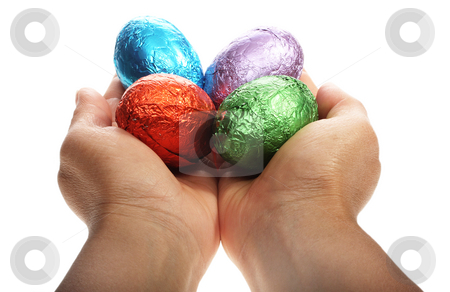 Hands holding four Easter eggs stock photo, Two hands holding chocolate Easter eggs isolated with area for text by Christopher Meder
