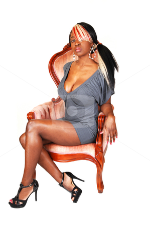 Jamaican women in armchair. stock photo, A beautiful jamaican woman with long colored hair, sitting in an pink armchair  with a nice gray dress and long legs. by Horst Petzold