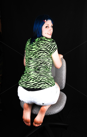 An lovely blue haired girl. stock photo, A beautiful blue dyed hair girl, kneeling backwards on an office chair in the green and black top and white shorts for black background. by Horst Petzold