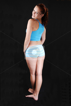 Woman in exercise clothing. stock photo, A young girl in workout pants and top standing in the studio and shooing her nice figure and butt, for black background. by Horst Petzold