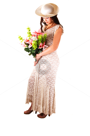 Woman with hat and lilies. stock photo, Beautiful lady in a beige long dress and hat standing in the studio with  pink lilies in her arm smiling, for white background. by Horst Petzold
