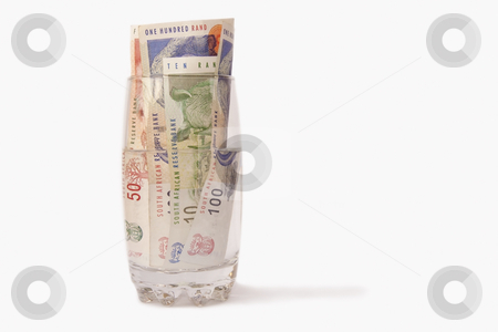 Money and water stock photo, South African Money in a glass of water, isolated on a white background by Chris Alleaume