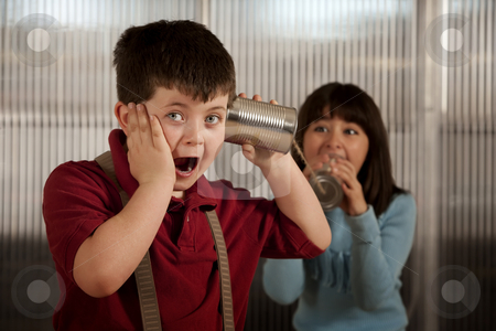 Little boy getting shocking message on tin can phone stock photo, Little boy getting shocking message from girl on tin can phone by Scott Griessel