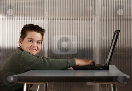 Boy working on a laptop computer stock photo, Cute young boy working on a laptop computer by Scott Griessel