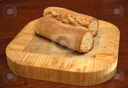 Homemade Rye Caraway Bread stock photo, Homemade rye caraway bread cut in half on a wooden cutting board on a table. by Denis Radovanovic