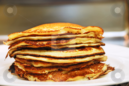 Pile of Pancakes stock photo, Close up of a pile of pancakes served on a white plate. by Denis Radovanovic