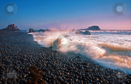 Sunset Wave Explosion stock photo, A wave exploding over a boulder on Cobble beach along the Oregon Coast by Mike Dawson