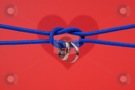 Wedding stock photo, Connected strings with golden wedding rings on red background by Jolanta Dabrowska