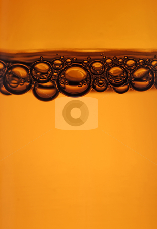 Beer bubbles stock photo, Close up of bubbles at the top of a beer bottle by Paul Turner