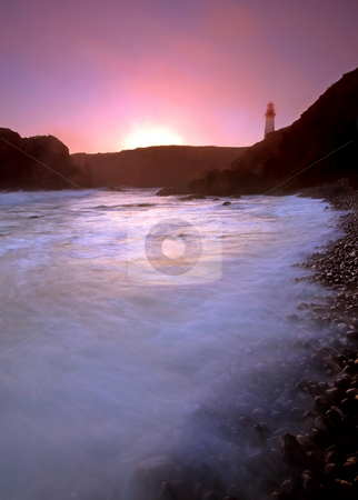 Cobble Beach Sunset stock photo, The setting sun on a foggy evening at Yaquina Head Lighthouse by Mike Dawson