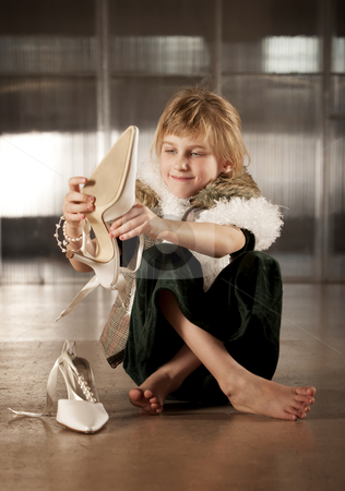 Cute young girl putting on adult shoe stock photo, Cute young girl in dress-up clothes putting on pointy shoe by Scott Griessel