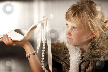 Cute young girl looking scornfully at an adult shoe stock photo, Cute young girl in dress-up clothes looking at a pointy shoe by Scott Griessel